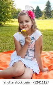 Little girl smelling blossoming flowers in summer