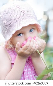 Little girl smelling a pink rose