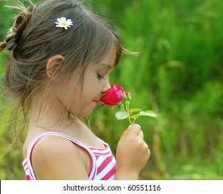 Little girl smelling a red rose
