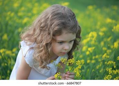 Little girl smells a bittercress flower on a glade