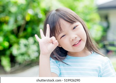 little girl smile happily and show ok to you in the park,asian