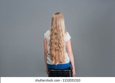 Little girl smile with long blond hair on grey background. Happy child with fashion hairstyle. Beauty kid smiling with adorable look. Beauty salon. In this salon we love hair.