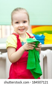 Little girl with smile on face in red sundress with green towel in hands