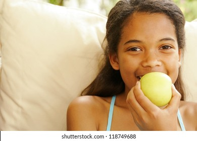 Little girl smiles in anticipation as she starts to eat an apple