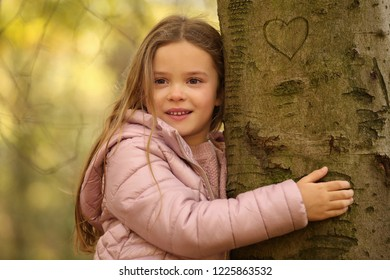 Little girl smiles and huggs a tree