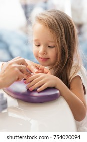 Little girl smiles while woman makes her manicure in beauty saloon