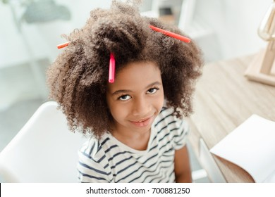 Little girl smiling at camera with markers in her curly hair