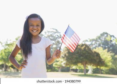 Little girl smiling at camera waving american flag on a sunny day