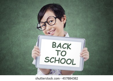 Little girl smiling at the camera while holding a digital tablet with text of Back to School in the class