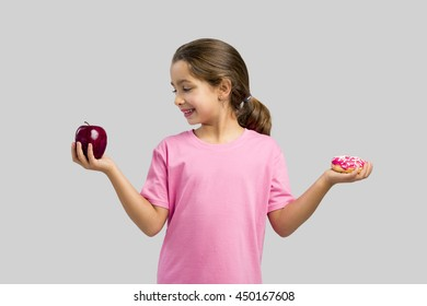 Little girl smiling and choosing between a apple and a donut