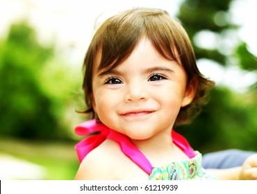 Little girl smiling, closeup portrait outdoors