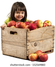 Little girl smiling with crate full of apples.