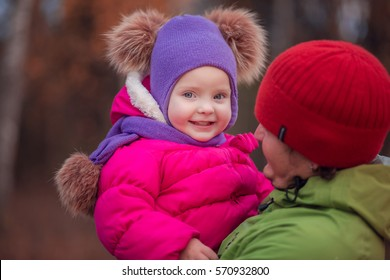 Little girl smiling at daddy on hands in autumn forest