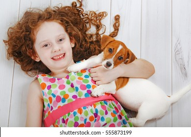 Little girl is smiling and embracing her friend pet, lying on a wooden floor. Healthy smile, happy childhood concept.
