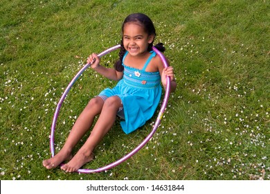 Little girl smiling in the grass playing with a hula hoop. Horizontally framed photograph