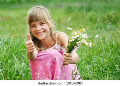The little girl is smiling  in the grass and thumbup