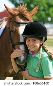 A little girl smiling with her horse