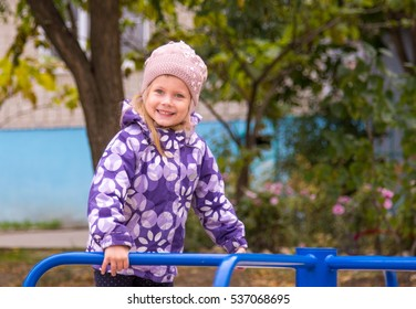 Little girl smiling holding on to the metal railing of children's slides in the yard