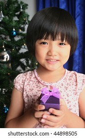 Little girl smiling and holding purple gift box