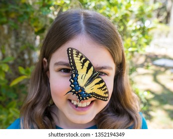 Little girl smiling with large butterfly on her face.