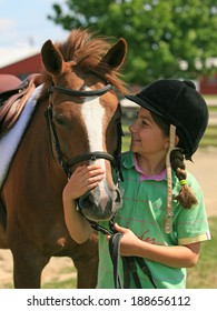 A little girl smiling and looking at her horse