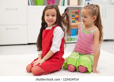 Little girl smiling meanwhile her girlfriend combing hair
