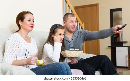 Little girl and smiling parent sitting with popcorn in front of TV. Focus on girl