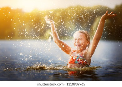 little girl smiling playing in the river. A girl with blond hair raises her hands up in the water and splashes water drops.