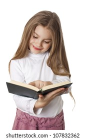 Little girl smiling and reading a book