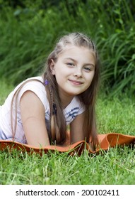 A little girl smiling as she lies in the fresh spring grass.