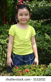 Little girl smiling and standing alone in the garden