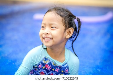 Little girl smiling at swimming pool and she feeling happy.