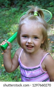 Little girl smiling while standing with a badminton racket