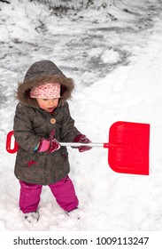 little girl with a snow shovel