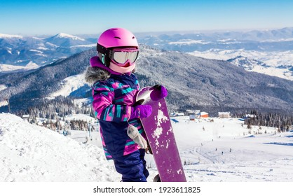 Little girl snowboarding with equipment helmet and goggles outwear holding snowboard resting on top of ski slope in sunlight