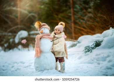 Little girl with snowman in winter park