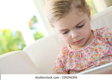 Little girl in sofa connected with digital tablet