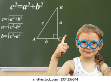 Little girl solves the problem on a blackboard. Wunderkind