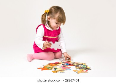Little girl is solving puzzle on white background
