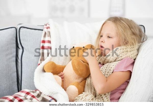 Маленькая девочка с больным горлом держа игрушка медведь крупным планом