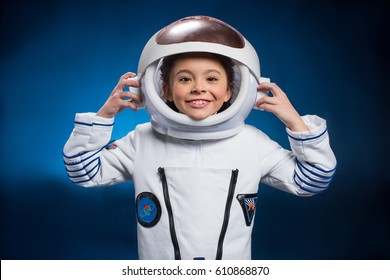 Little girl in space suit wearing helmet  and smiling at camera