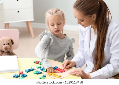 Little girl with speech therapist composing words of letters in office