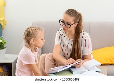 Little girl with speech therapist reading book in office