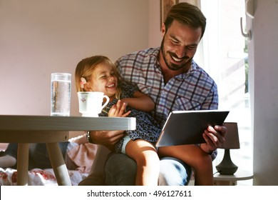 Little girl spending time with her father at home.