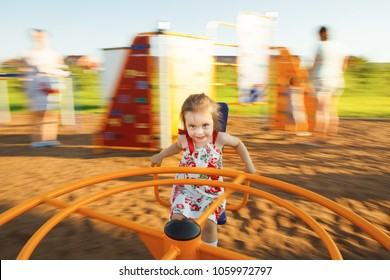little girl spinning on a children's carousel among the playground.
