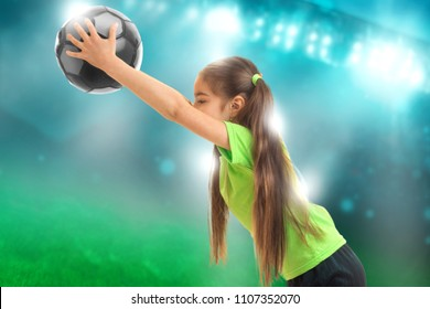 little girl in sports uniform plays soccer ion football stadium
