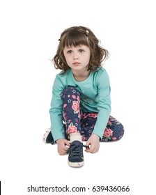 A little girl, in sportswear, ties the shoelaces while sitting on the floor. She is tired. White isolated background.