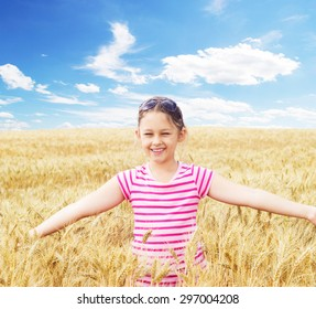 little girl spreading her arms in the wheat field