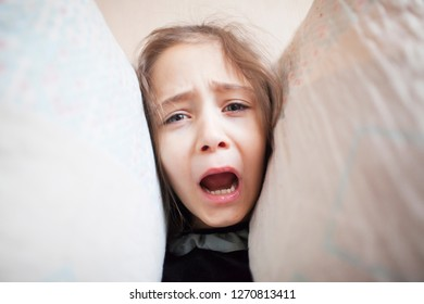 Little girl squeezes her head with pillows