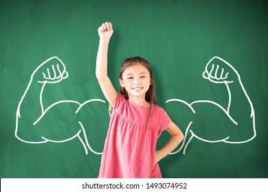 little girl standing against chalkboard and strong winner concept
